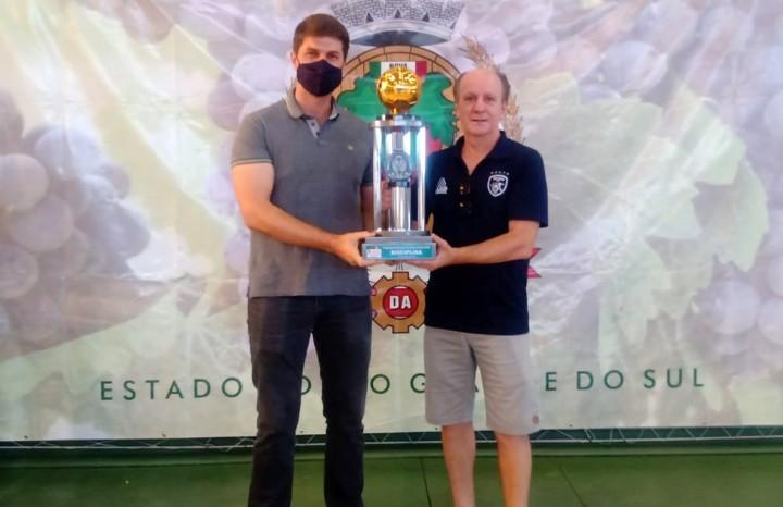 O técnico do Bola Bola, Luiz Carlos Tonin, recebe o troféu de campeão das mãos do prefeito César Ulian